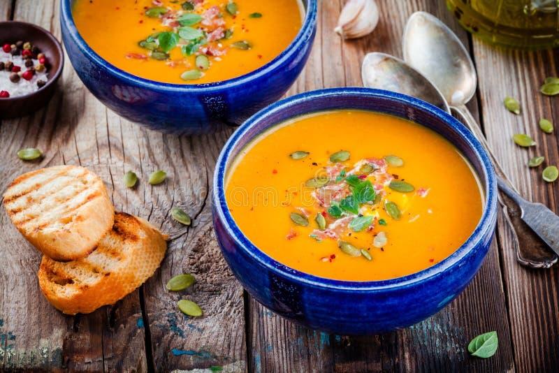 De eigengemaakte soep van de de herfst butternut pompoen met pompoenzaden, bacon en basilicum royalty-vrije stock afbeelding