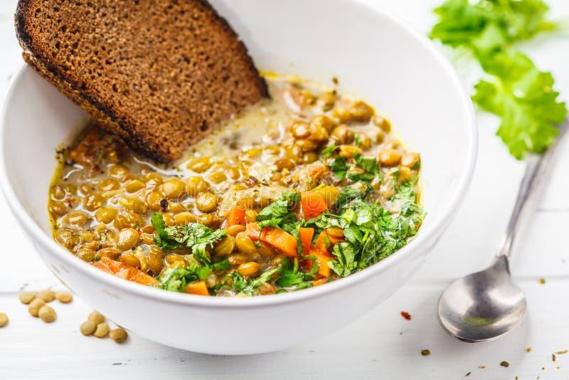 De eigengemaakte soep van de veganistlinze met groenten, brood en koriander royalty-vrije stock fotografie