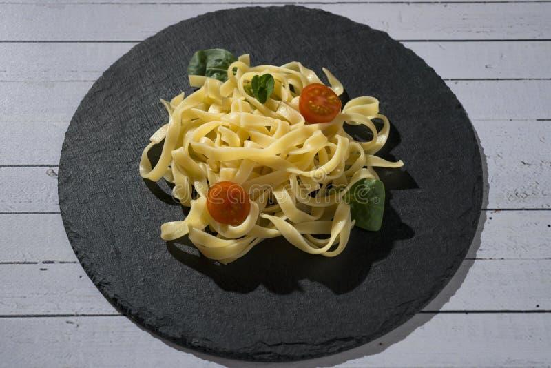 De eigengemaakte verse schotel van de deegwarenspaghetti met tomaat en orego stock fotografie