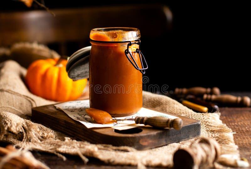 De eigengemaakte zoete en smakelijke het glaskruik van de pompoenkaramel n bevindt zich op houten raad stock fotografie