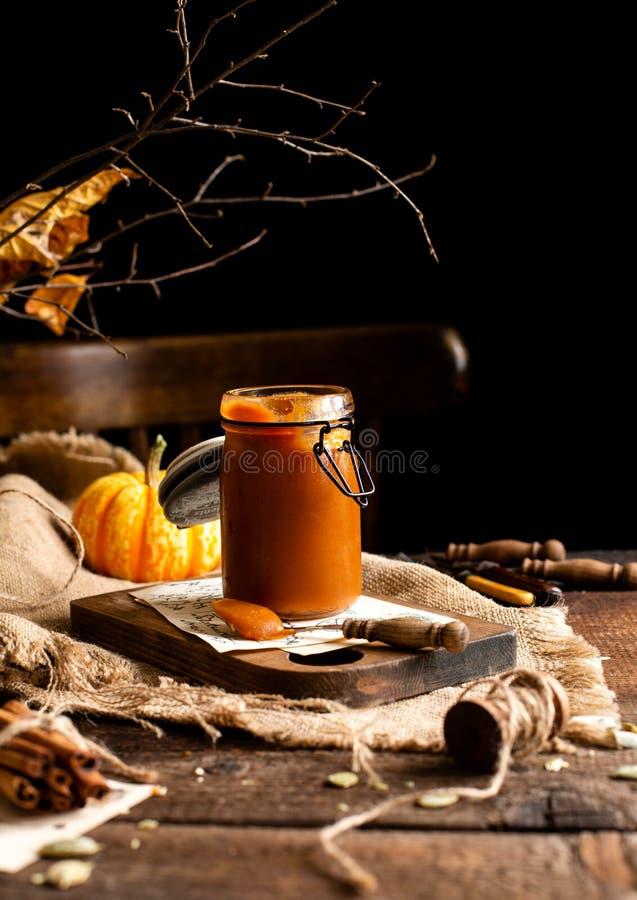 De eigengemaakte zoete en smakelijke het glaskruik van de pompoenkaramel n bevindt zich op houten raad royalty-vrije stock foto's