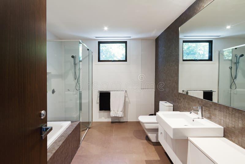 De eigentijdse bruine natuurlijke badkamers van de tonenfamilie royalty-vrije stock afbeelding
