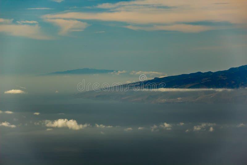De eilanden van La Gomera en van Gr Hierro, die in de lucht tussen verschillende wolken vliegen Heldere blauwe hemel Weergeven va royalty-vrije stock foto