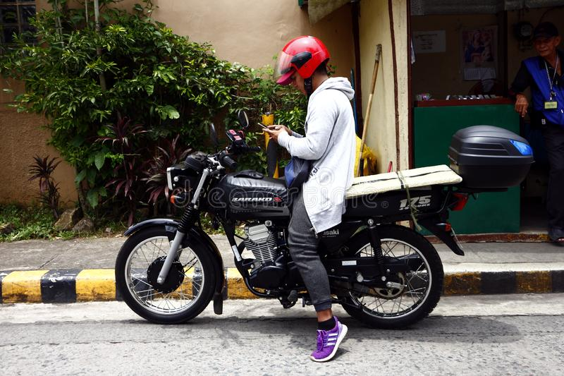 De einden van een motorfietsbestuurder bij een stoep om op zijn smartphone te controleren royalty-vrije stock afbeeldingen