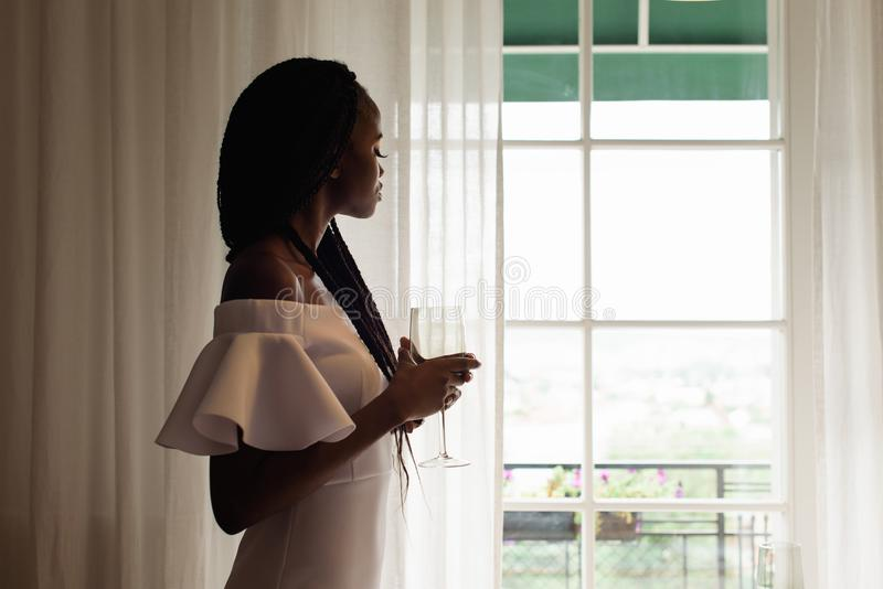 De elegante aantrekkelijke Afrikaanse dame met het wijnglas kijkt door het venster Zij draagt witte kleding royalty-vrije stock foto's