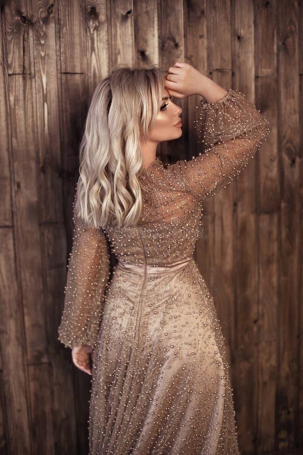 De elegante blonde vrouw in beige parels kleedt het stellen tegen houten muurachtergrond met exemplaar ruimtegebied Manier mooie  stock foto's