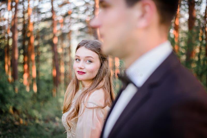 De elegante bruid met rode lippen bewondert knappe bruidegom stock afbeelding