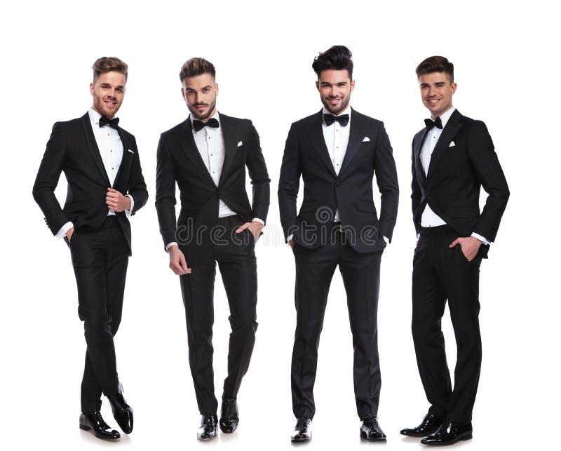 De elegante groep van vier mensen die bevinden zich met dient zakken in royalty-vrije stock foto's