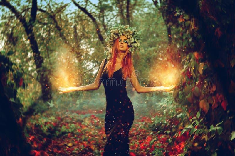 De elegante heks van het redhairmeisje tovert in het magische bos royalty-vrije stock fotografie