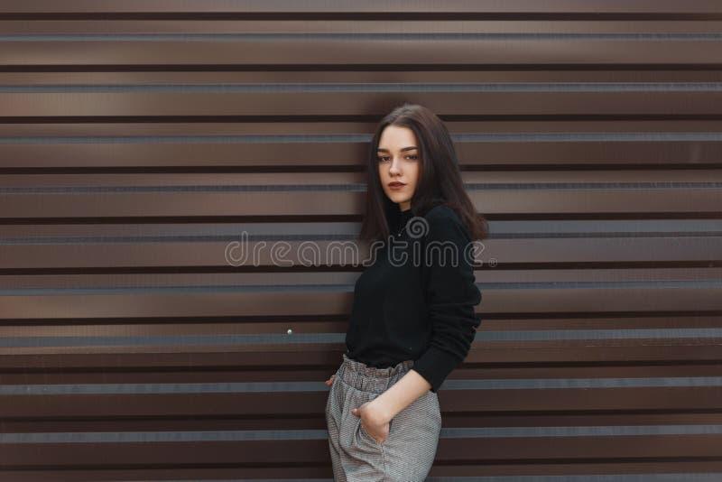 De elegante jonge donkerbruine vrouw met natuurlijke samenstelling in een zwarte uitstekende sweater in geruite broek bevindt zic royalty-vrije stock afbeeldingen