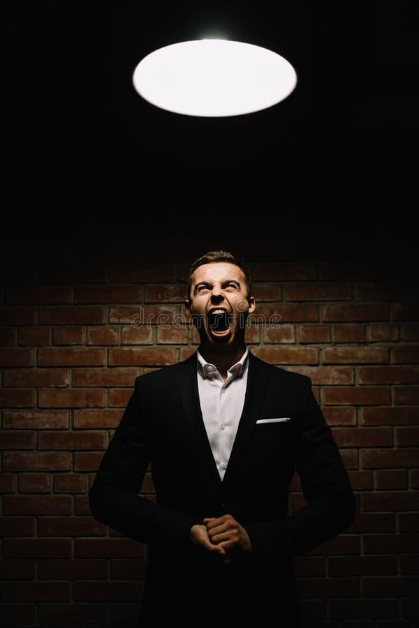 De elegante jonge maniermens in smoking houdt allebei van hem indienen stock fotografie