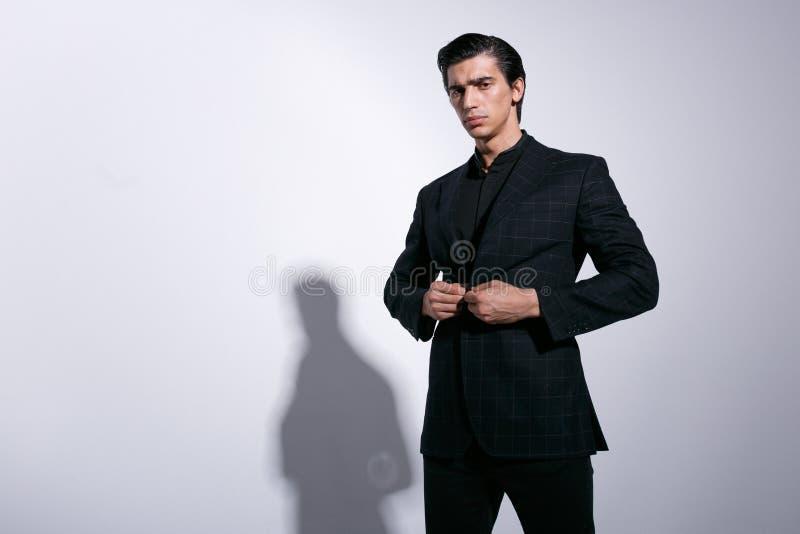 De elegante jonge mens in volledig zwart kostuum, schikte zijn die jasje, bekijkend ernstig camera, op een witte achtergrond word stock foto's
