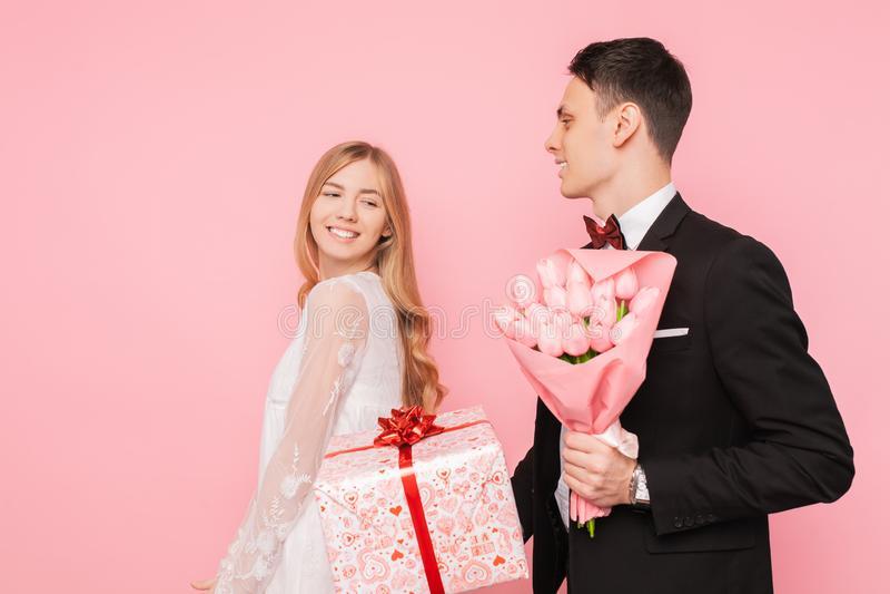 De elegante man in een kostuum maakt tot een verrassing aan een vrouw, geeft een boeket van bloemen en een doos met een gift, op  stock fotografie