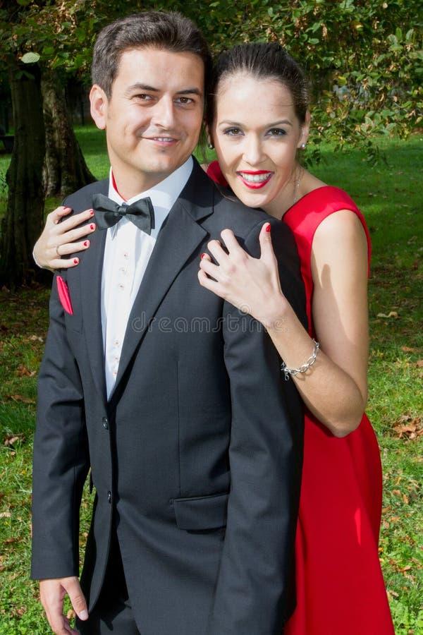 de elegante man terwijl het houden van zijn rode vrouw van de minnaarkleding dient schouders in stock fotografie