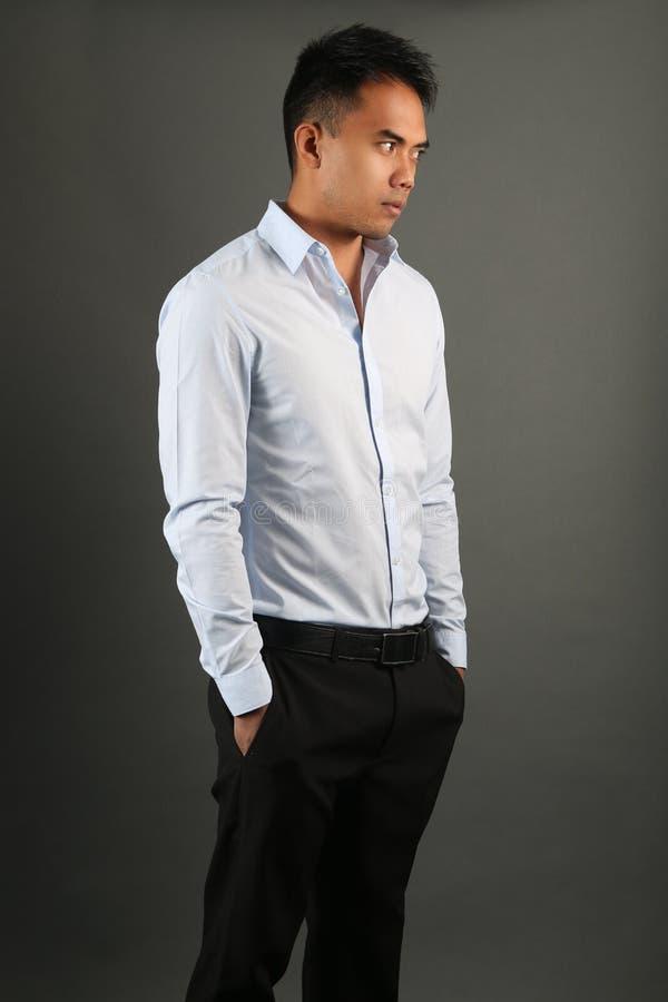 De elegante mens die een blauw overhemd en een zwarte dragen hijgt het stellen royalty-vrije stock foto