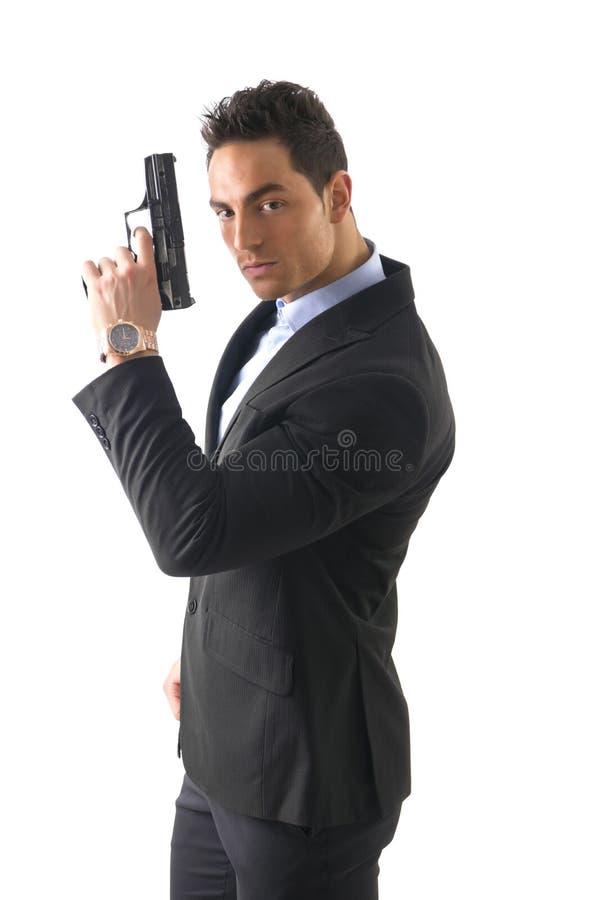 De elegante mens met kanon, kleedde zich als spion of geheim stock afbeelding