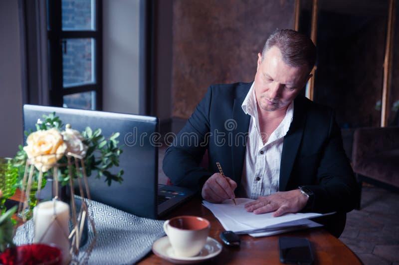 De elegante mens ondertekent documenten in luxeflats stock afbeelding