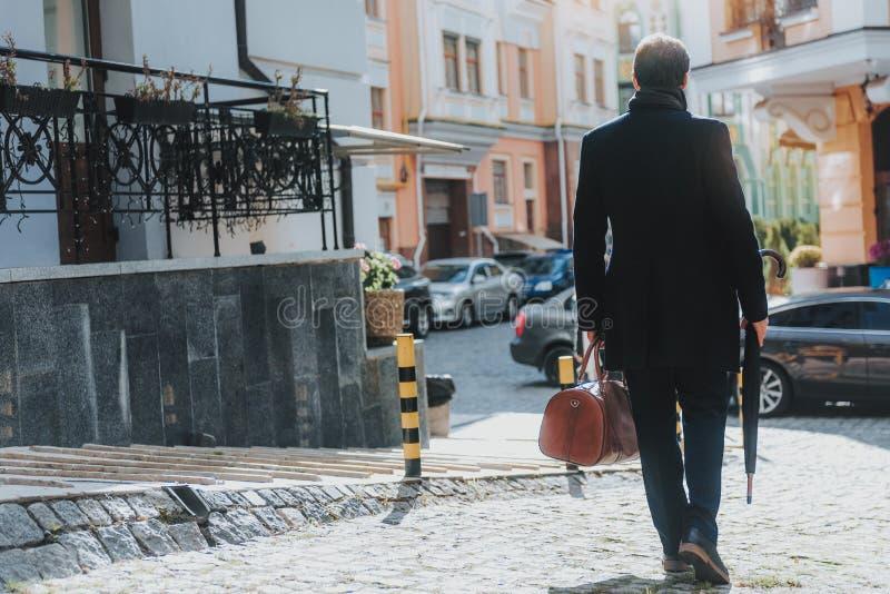 De elegante mens in zwarte laag loopt in stad royalty-vrije stock afbeeldingen