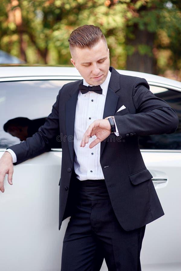 De elegante modieuze bruidegom die dichtbij auto zijn brite wachten en bekijkt horloge royalty-vrije stock afbeeldingen