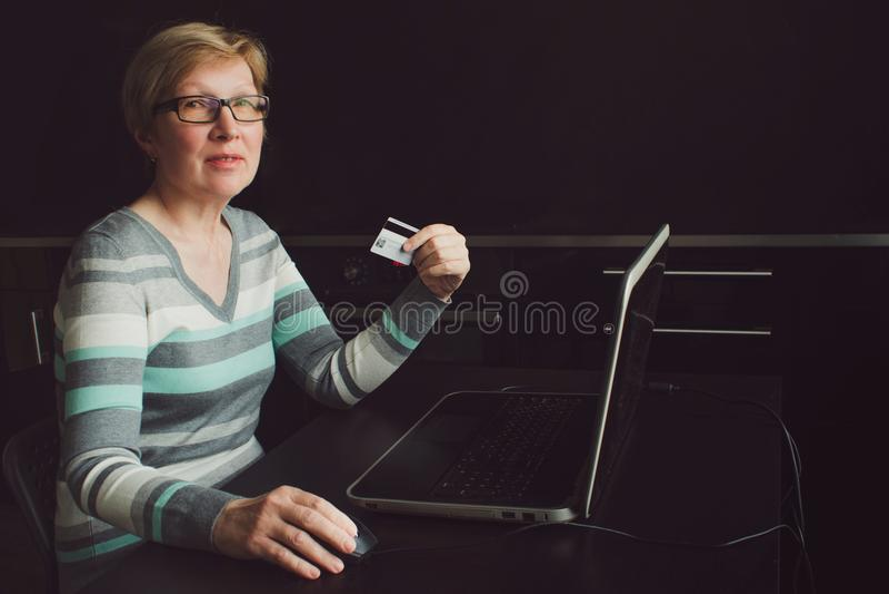 De elegante rijpe vrouw gebruikt Betaalpas voor online betalingen royalty-vrije stock afbeeldingen