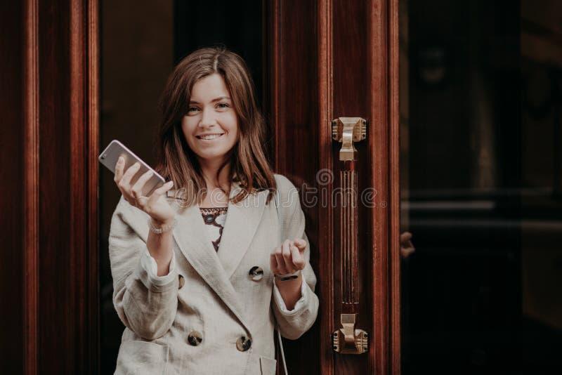 De elegante schitterende dame in regenjas, houdt mobiele telefoon, wacht op vraag, stelt openlucht dichtbijgelegen deuren, die vo stock afbeeldingen