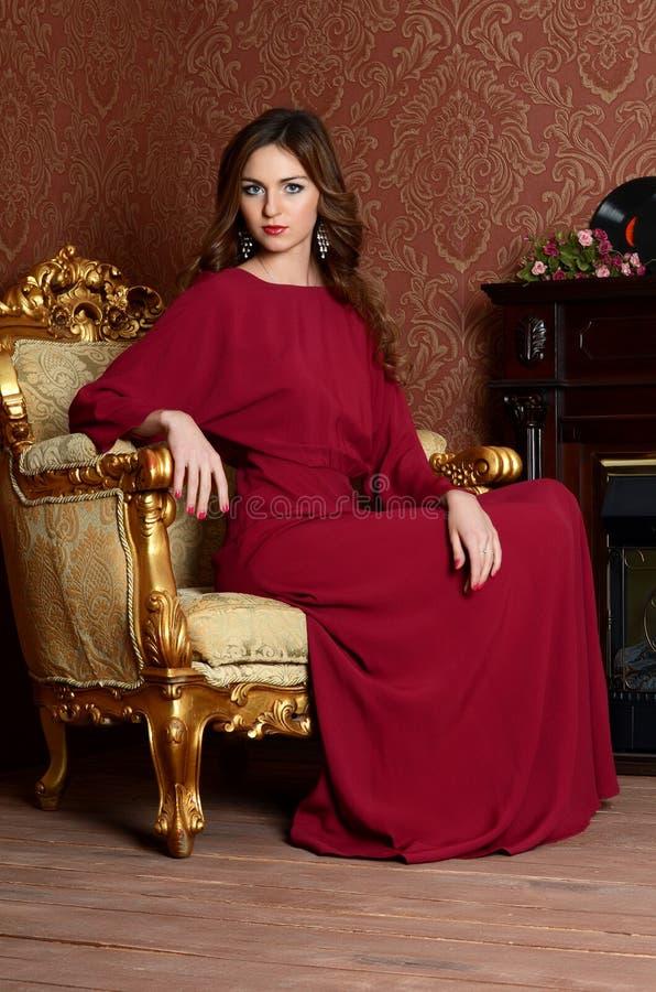De elegante sensuele jonge vrouw in een Bordeauxkleding royalty-vrije stock foto