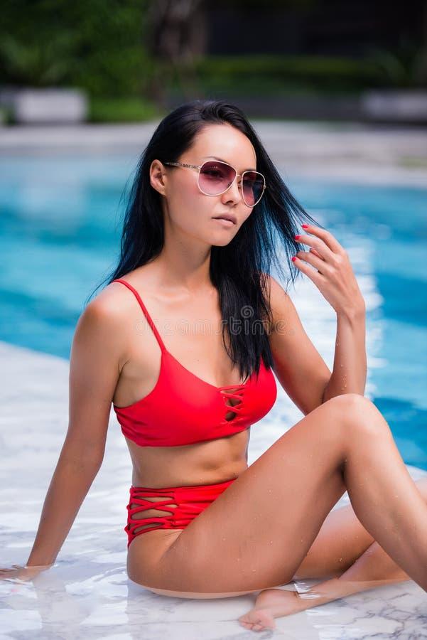 De elegante sexy vrouw in de rode bikini op het zon-gelooide slanke en goed gevormde lichaam stelt dichtbij het zwembad royalty-vrije stock afbeelding