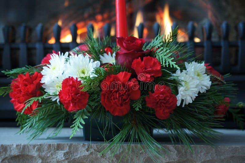 De elegante vertoning van de Kerstmisbloem met open haard het branden op de achtergrond stock foto