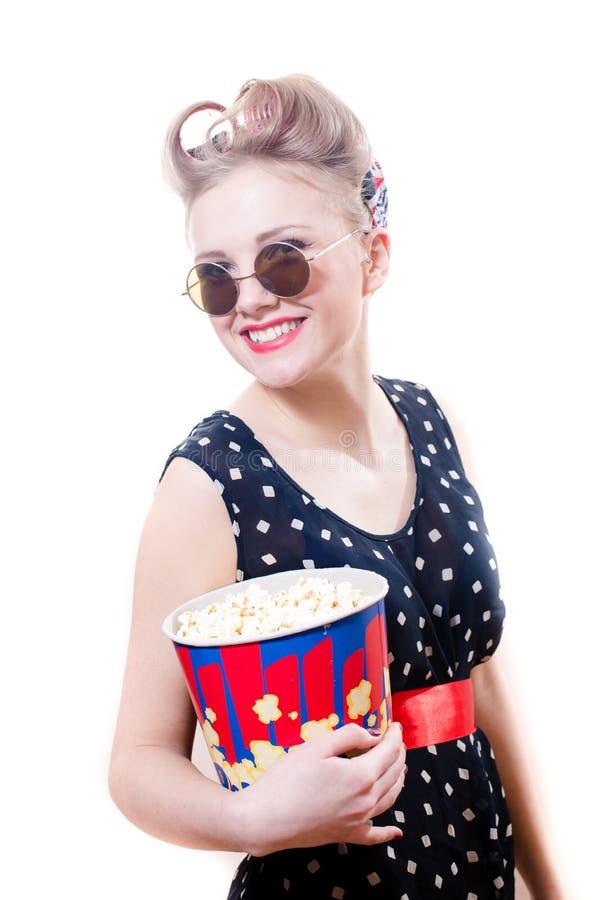 De elegante vrij grappige jonge blonde pinupvrouw die met krulspelden om zonnebril popcorn het gelukkige glimlachen houden bekijke royalty-vrije stock fotografie