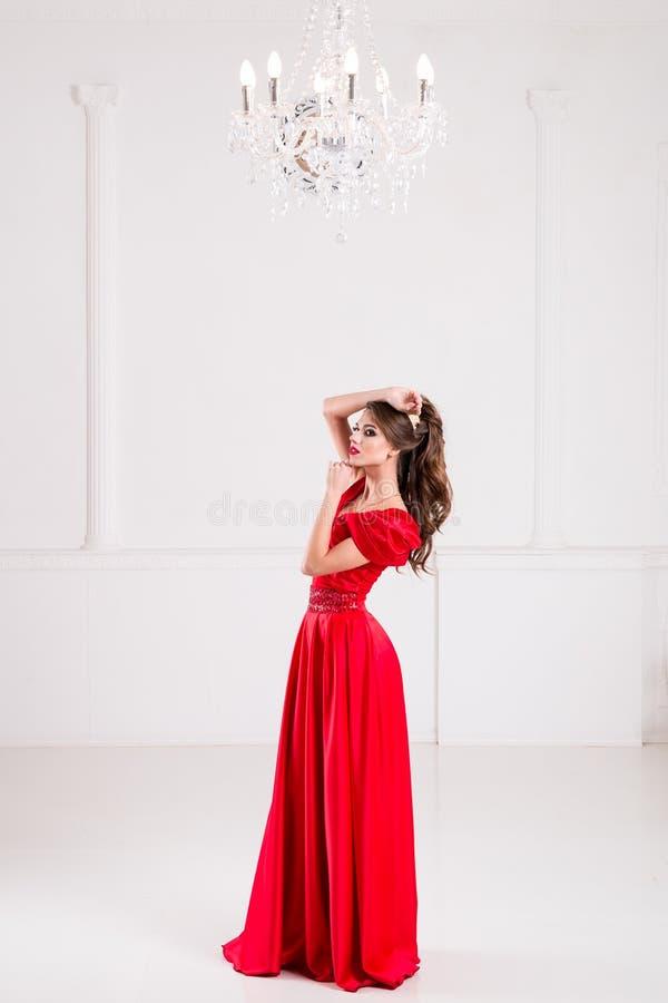 De elegante vrouw in een lange rode kleding bevindt zich in een heldere ruimte w royalty-vrije stock afbeelding