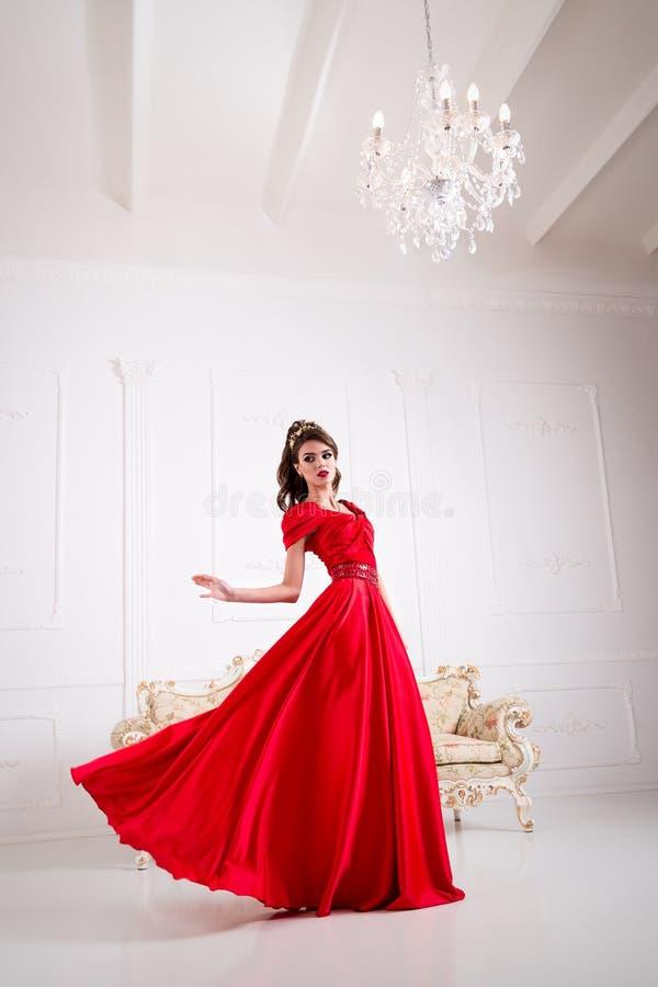 De elegante vrouw in een lange rode kleding bevindt zich in een witte ruimte, D royalty-vrije stock afbeeldingen