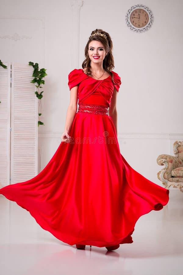 De elegante vrouw in een lange rode kleding bevindt zich in een witte ruimte, D royalty-vrije stock foto