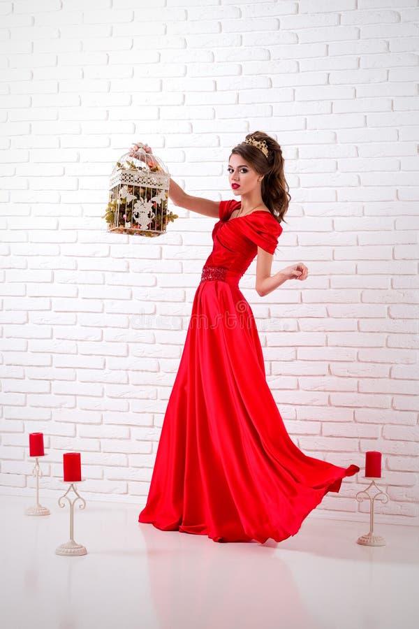 De elegante vrouw in een lange rode kleding bevindt zich in een witte ruimtewi royalty-vrije stock afbeelding