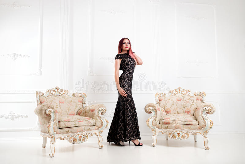 De elegante vrouw of het meisje in avond zwarte kleding bevinden zich in a royalty-vrije stock afbeeldingen