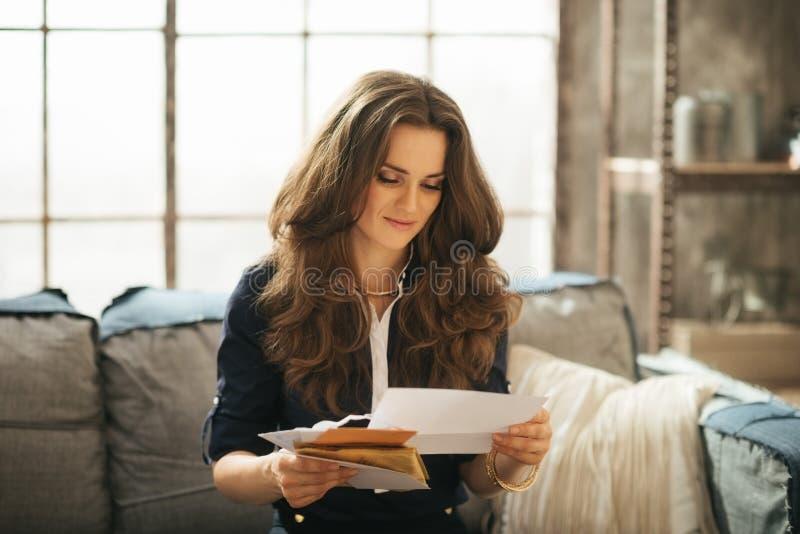 De elegante vrouw zit op laag en leest correspondentie stock afbeeldingen