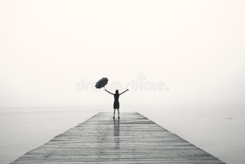 De elegante vrouw in zwarte verheugt zich met hun wapens omhoog in de regen royalty-vrije stock foto's