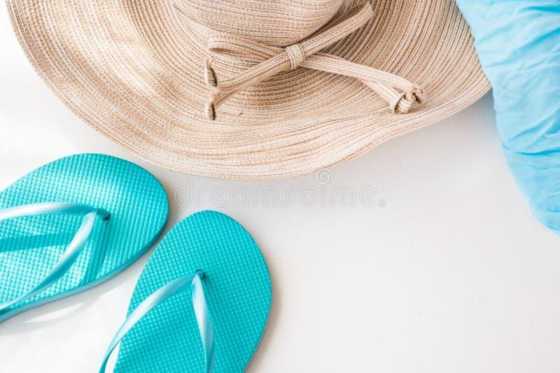 De elegante vrouwelijke strohoed, de blauwe pantoffels en het strand verpakken op concrete witte achtergrond, de zomervakantie, k royalty-vrije stock foto