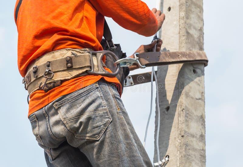 De elektricien beklimt het werken in de hoogte aan de pool met veiligheidsgordel royalty-vrije stock afbeelding