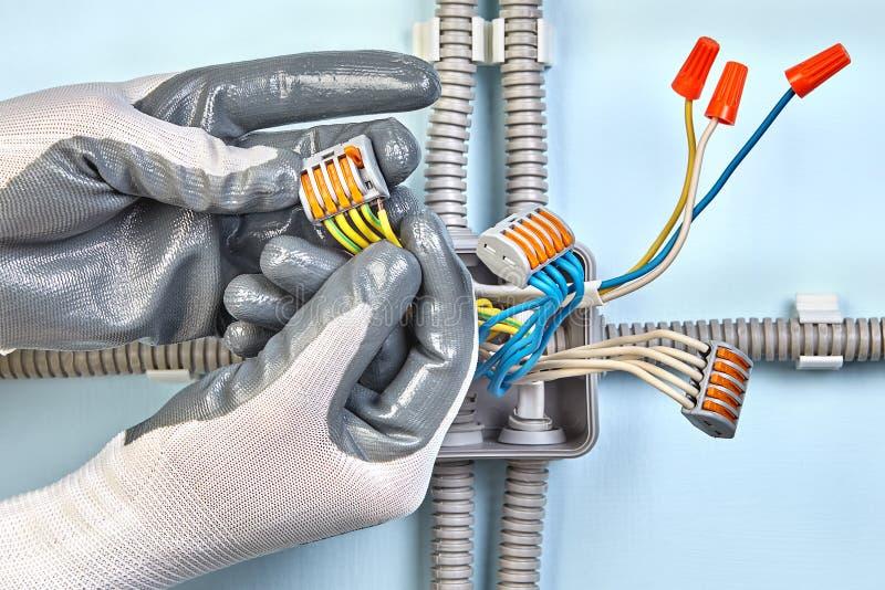 De elektricien in beschermende handschoenen zet kabeldoos op stock foto