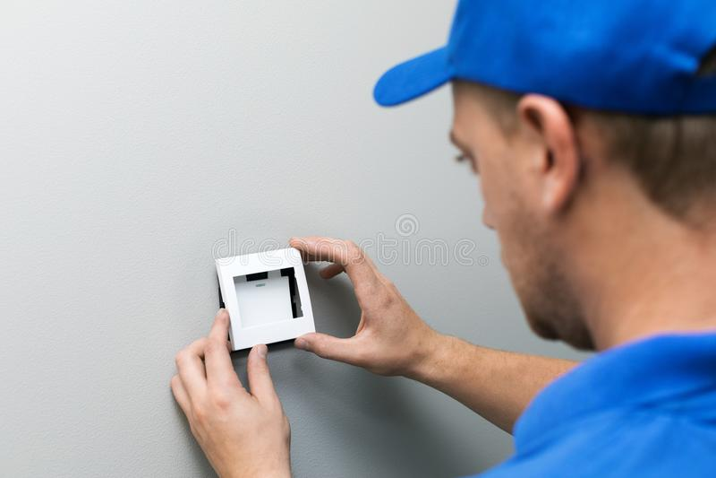 De elektricien die licht installeren schakelt de muur in royalty-vrije stock afbeeldingen