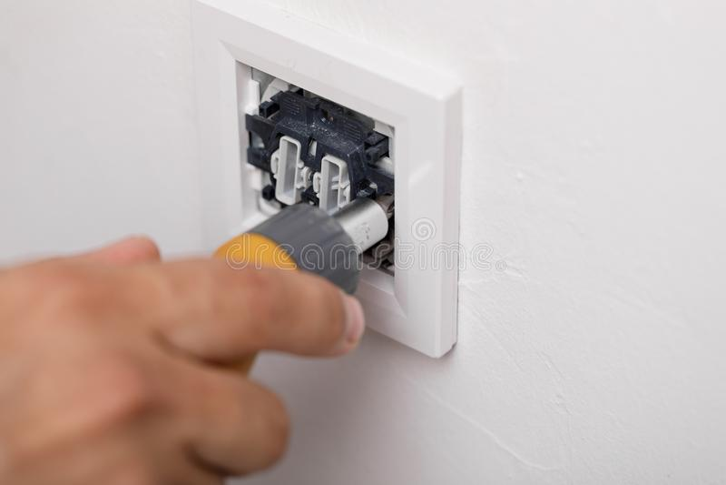 De elektricien die de lichte schakelaar installeren Hulpmiddel stock afbeelding