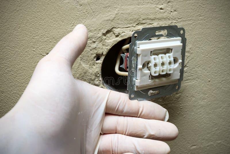 De elektricien dient handschoenen in installerend lichte schakelaar in muur stock fotografie