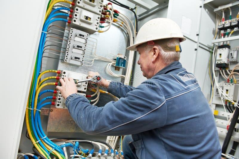 De elektricien haalt de schroeven met moersleutel aan