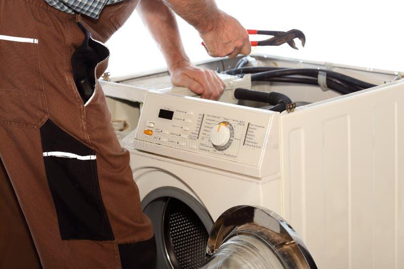 De elektricien herstelt een klerenwasmachine stock foto