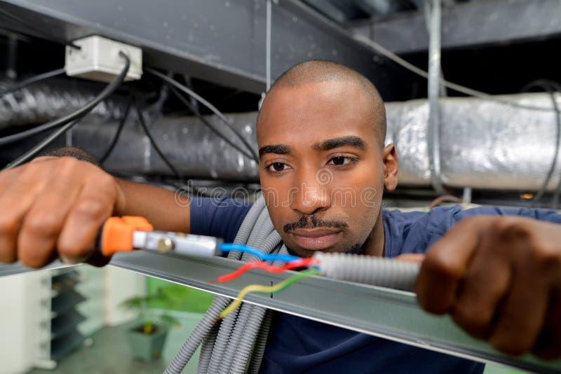 De elektricien houdt van zijn baan stock fotografie