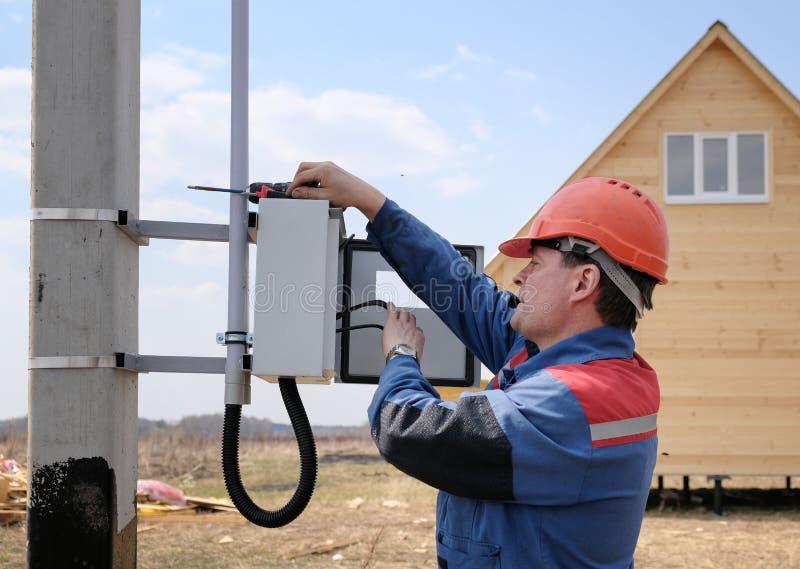 De elektricien nam in de installatie van elektriciteitsmeter in dienst op de steun van machtslijnen het proces van de elektricien royalty-vrije stock fotografie