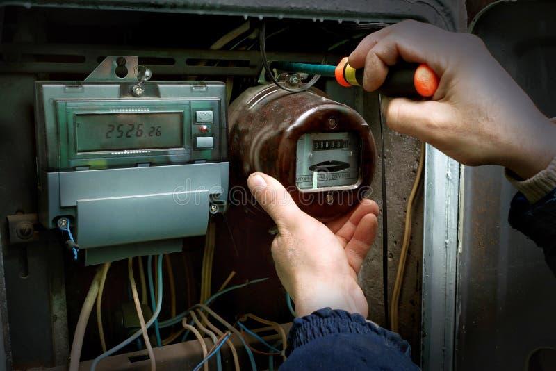 De elektricien ontmantelt de oude analoge elektriciteitsmeter royalty-vrije stock afbeeldingen