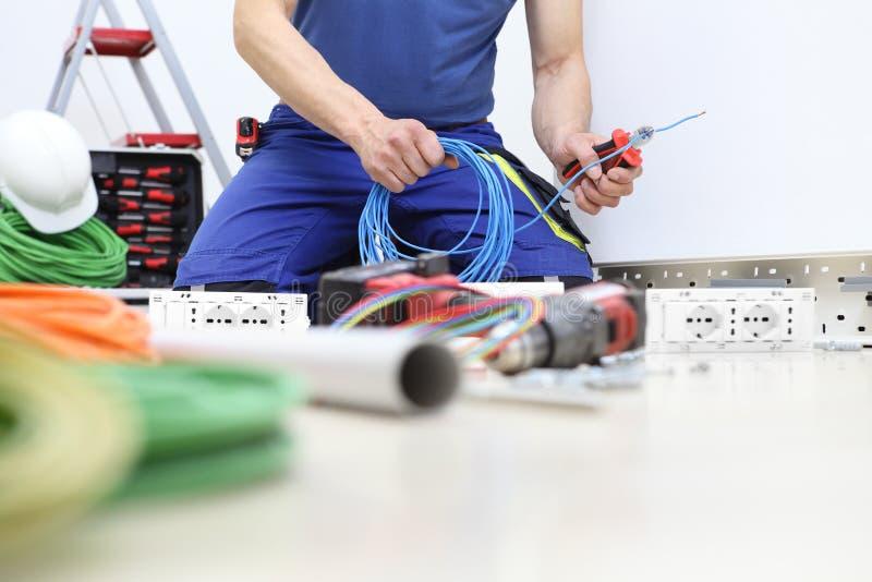 De elektricien op het werk met messenmazen in hand snijden de elektrische kabel installeren elektrische kringen, elektrobedrading stock fotografie