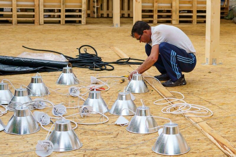 De elektricien zet het verlichtingssysteem op stock afbeelding