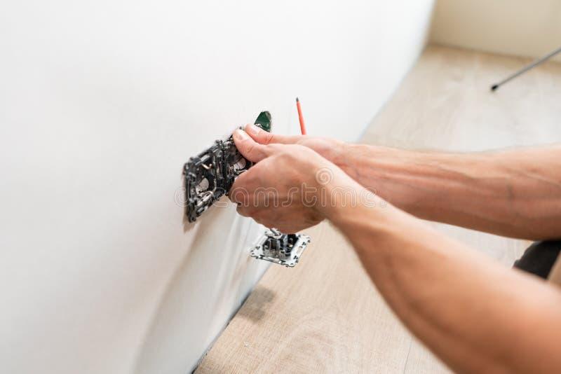 De elektricienarbeider installeert lichte schakelaar en contactdoos op muur in Witte ruimte Schroevedraaier, de handen van de clo stock afbeeldingen